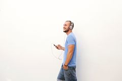Man walking with mobile phone listening to music on headphones Royalty Free Stock Images