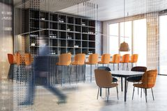 Man walking in modern white bar. Businessman walking in modern bar with white and wooden walls, concrete floor, bar counter and black tables with orange chairs royalty free stock image