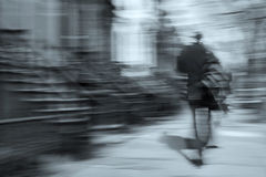 Man walking motion blur. Man walking on a city street in motion blur, brownstone buildings as a background, rear view Stock Photo