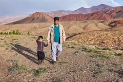 Man walking on mountain plateau with little boy, Abyaneh, Iran. Abyaneh village, Isfahan Province, Iran - April 26, 2017: A mature Iranian man walks down a royalty free stock photo