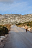 Man walking mountain road. ATHENS, GREECE - JANUARY 4, 2015: Man walking on Penteli mountain in Athens, Greece. Snow melting on sunny winter day Stock Image