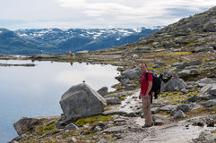 Man walking on a mountain trail in Norway. Path to Trolltunga or Royalty Free Stock Photos