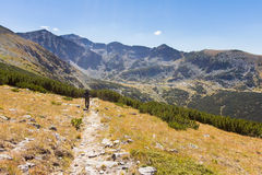 Man walking mountains trail. Stock Photos