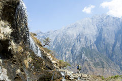 Man Walking by Mountainside Waterfall. A hiker walks past a waterfall flowing down the steeps canyon walls of Tiger Leaping Gorge in Yunnan Province, China Royalty Free Stock Photography