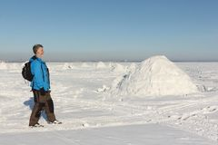 Man walking near an igloo on a snowy reservoir in winter. Novosibirsk, Russia Royalty Free Stock Images
