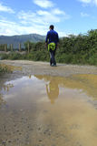 Man walking near a puddle with a reflection. Of him Royalty Free Stock Photos