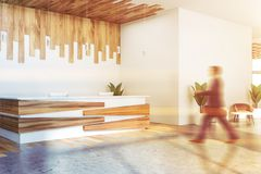 Man walking near white reception desk. Businessman walking in office hall with white and wooden walls, concrete floor and white and wooden reception counter royalty free stock image
