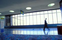 Man walking near windows. A man walking down an airport hallway or concourse in front of a row of windows Stock Photos