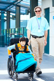 Man walking next to little boy in wheelchair outside medical fac Stock Image