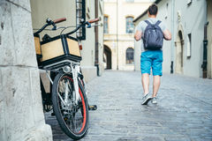 Man walking by old european city street bicycles parked near the wall Stock Photos