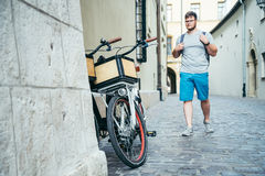 Man walking by old european city street bicycles parked near the wall Royalty Free Stock Images