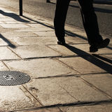 Man walking on old pavement. The legs of a man wearing black trousers and leather shoes, walking on a sidewalk covered with old pavement in Paris, France royalty free stock image