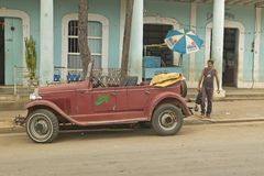 Man walking from old stores in rural Cuba to old beat-up car advertising a restaurant Stock Images