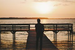 Man Walking Out on Dock of Water at Sunset Royalty Free Stock Photos
