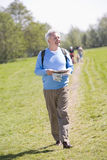 Man walking outdoors holding map smiling Stock Photo