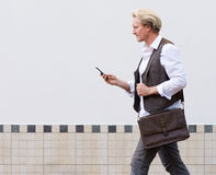 Man walking outdoors and looking at mobile phone. Side portrait of man walking outdoors and looking at mobile phone royalty free stock image
