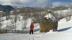 Man walking outside on mountain at the countryside through the snow along a haystack stock footage
