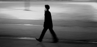 Man walking over cobblestone pavement. Dynamic night scene, Person almost focused, rest if the picture shows motion blur. Black&White royalty free stock photo