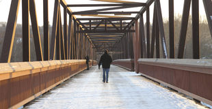 Man walking over footbridge Stock Image