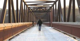 Man walking over footbridge. Rear view of a man walking across a pedestrian footbridge in the snow Stock Image
