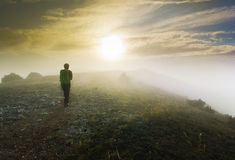 Man walking over a hill in foggy weather at sunset Stock Images