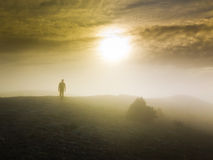 Man walking over a hill in foggy weather at sunset Royalty Free Stock Images