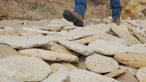 Man walking over rocks and sand