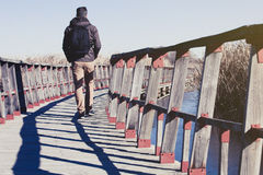 Man walking over a wood bridge in the nature, with a backpack. Stock Image