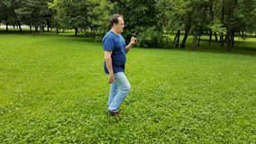 Man walking in the park with smartphone stock video