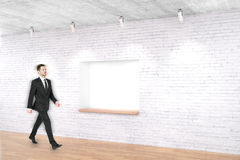 Man walking past built-in-wall seating. Young man walking past built-in-wall seating in concrete room. Mock up, 3D Rendering Stock Images