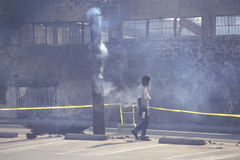 Man walking past burned industrial building Stock Image