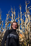 Man walking past corn field. A young man walks down a small country land past a field of corn Stock Images