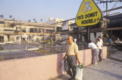 Man walking past donut shop destroyed during 1992 riots, South Central Los Angeles, California Royalty Free Stock Images