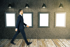 Man walking past frames. Young businessman walking past blank picture frames in room with dark concrete wall, wooden floor and ceiling lamps. Mock up, 3D Stock Photos