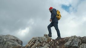 Man walking at the peak of a mountain at sunset in slow motion, Norway, Europe. Wearing a jacket, red hat and yellow. Man walking at the peak of a mountain at stock video footage