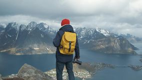 Man walking at the peak of a mountain at sunset in slow motion. Wearing a jacket, red hat and yellow backpac. Norway. Man walking at the peak of a mountain at stock footage