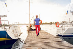Man walking on pier against yachts at sunny day Stock Photos
