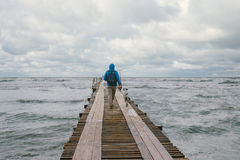 Man walking on pier on the background of stormy sea Stock Photography