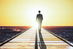 Man is walking on pier to meet light concept Royalty Free Stock Image