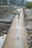 Man walking on pipeline Stock Photography