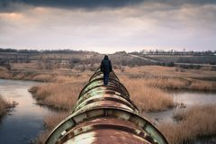 Man Walking On A Pipeline