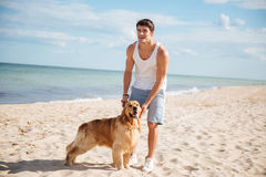 Man walking and playing with his dog on the beach Royalty Free Stock Photography