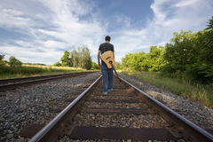 Man Walking Rail Road Tracks with Guitar Royalty Free Stock Photography