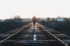 Man walking on railroad bridge Royalty Free Stock Image