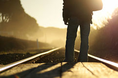 Man walking railroad tracks soul searching heavy fog mist in distance