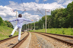 Man walking on railroad tracks in summer day Stock Images
