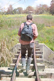 Man Walking on a Railway Bridge. Young Man on a Field Trip in Nature Crossing an old Railway Bridge Royalty Free Stock Photos
