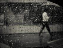 Man walking in rain with umbrella. See through window Royalty Free Stock Photo
