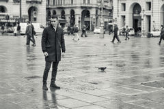 Man walking in rainy square in Europe Royalty Free Stock Photography