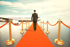 Man walking on red carpet to the first class of plane Stock Photos